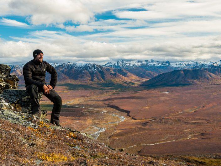 Naturfotograf sitzt auf Berg, Blick in den herbstlichen Denali Nationalpark, Alaska