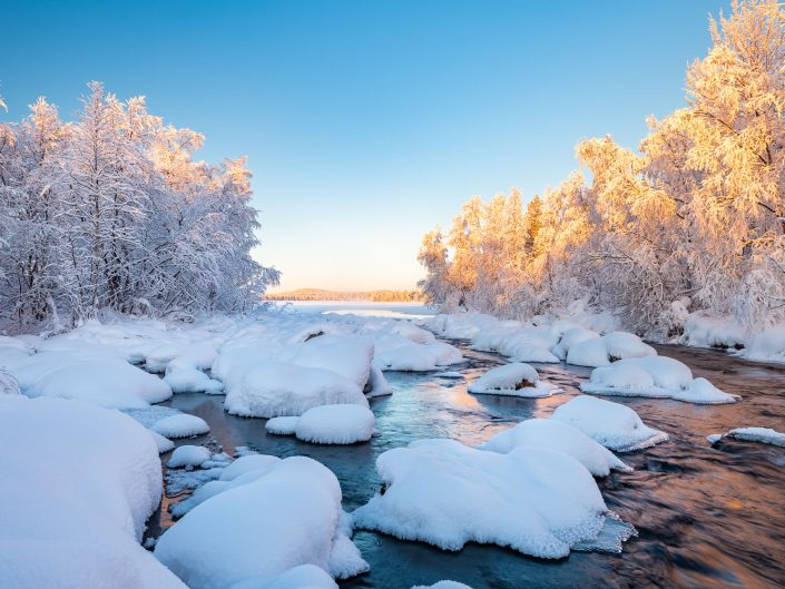 Verschneite Winterlandschaft mit Fluss, bei Muonio, Finnland