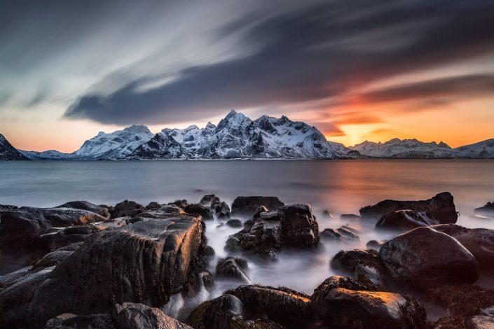 felsige Küste mit verschneiten Bergen bei Sonnenuntergang, Vareid, Lofoten