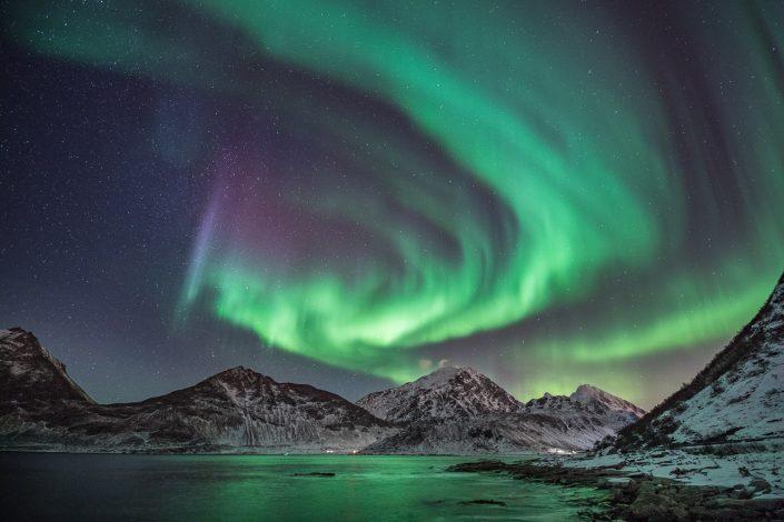 Nordlicht über verschneiten Bergen der Lofoten