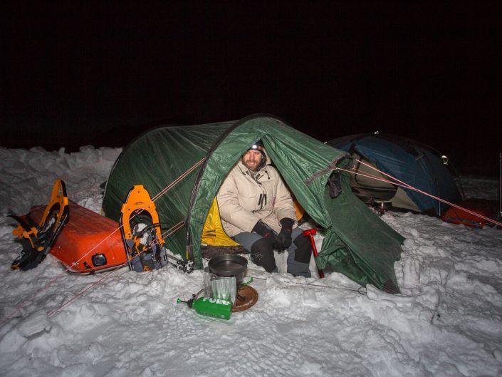 Mann im Zelt, im Winter beim Schneeschmelzen, Dovrefjell Nationalpark, Norwegen