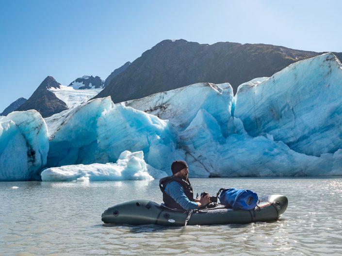 Naturfotograf mit Kamera sitzt in Packraft und fotografiert Gletscher, Alaska